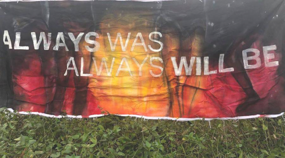 "Banner at Djab Wurrung Protection Embassy with Aboriginal colours says ""always was, always will be"" and grass in foreground"
