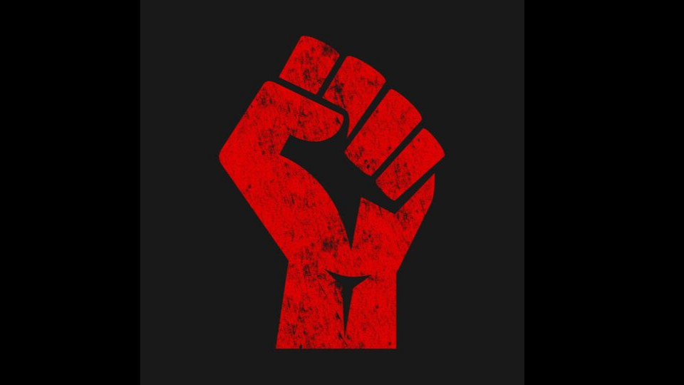 Raised fist in red on a black background