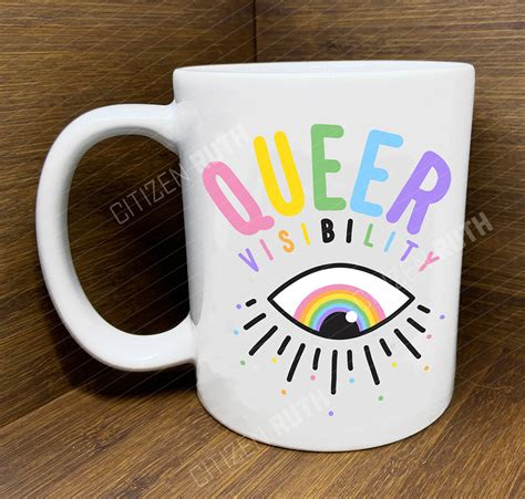 beverage mug with word queer in rainbow colours and eye with lashes