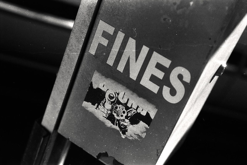 Sign with 'FINES' in black and white, with a sticker with a gun underneath