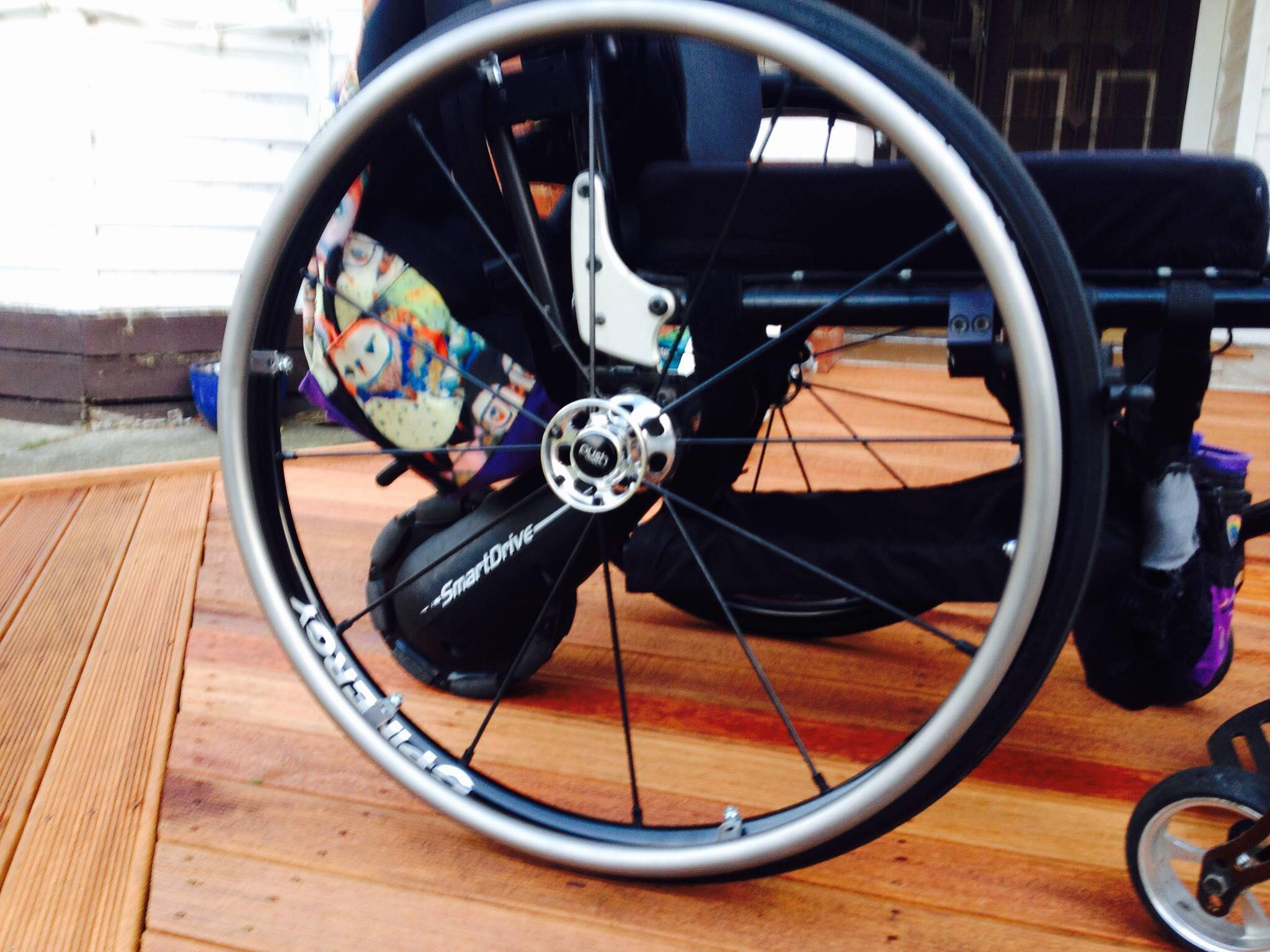 Image of a wheel of a wheelchair on a wooden floor, a owl printed bag can be seen hanging on the back