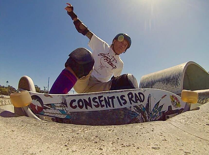 "A low-angle photograph of a skateboarder in the middle of a trick on the rim of a skate park bowl. You can see the bottom of their board, which has a large sticker on it reading ""Consent is Rad""."