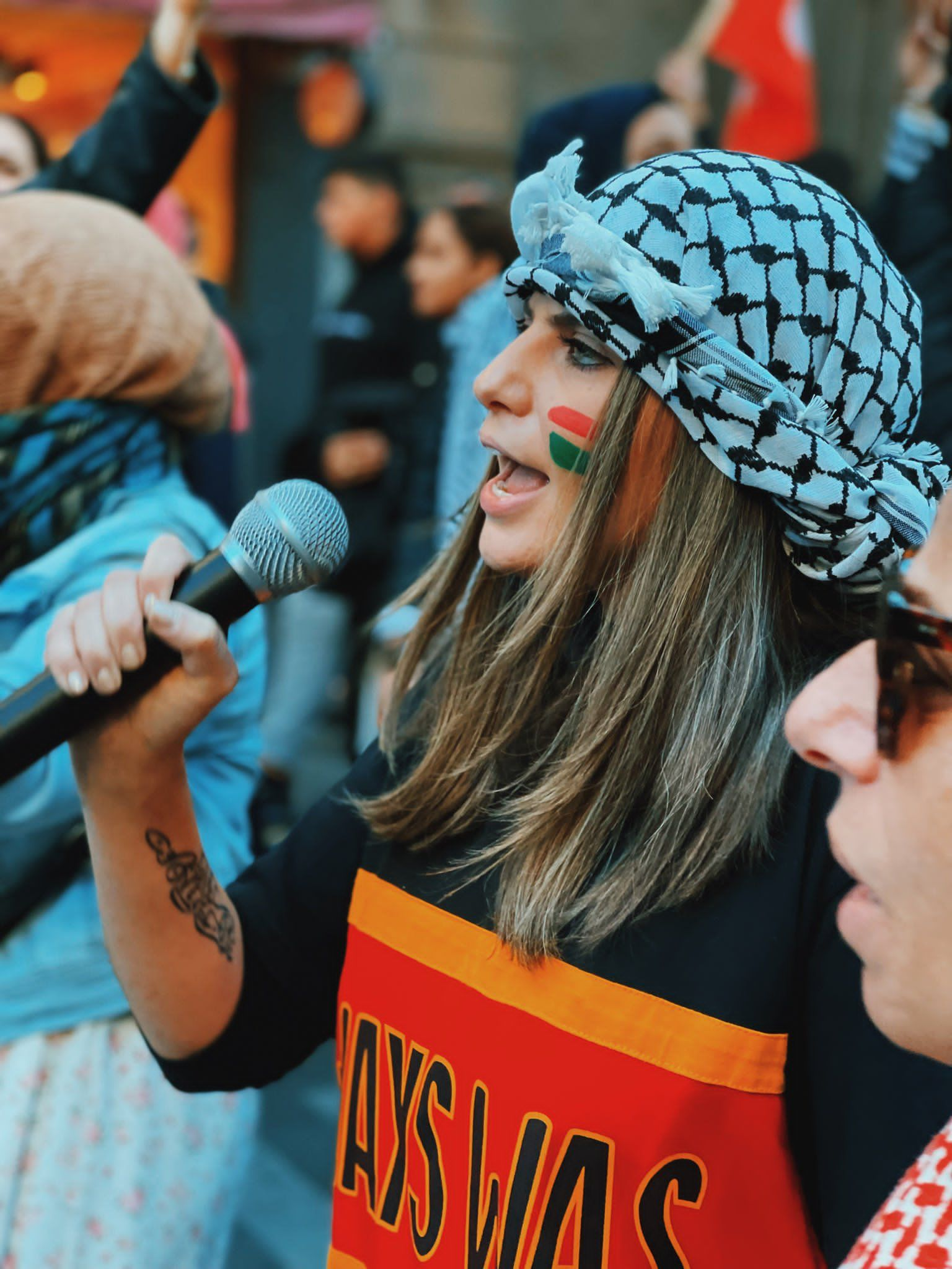 Palestinian activist, campaigner, and storyteller Jeanine Hourani speaks to a microphone at a protest. She is wearing a black and white kuffiyeh (كُوفِيَّة) with a black, yellow and red Always Was (Aboriginal land) sweater