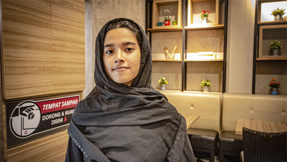 Nur Azizah is one of three people , refugees, appearing in the Freedom Street Documentary stuck in Indonesia as a result of Australia's border policies. Azizah is wearing black and looking definantly at the camera. Image courtesy of Freedom Street Documentary.