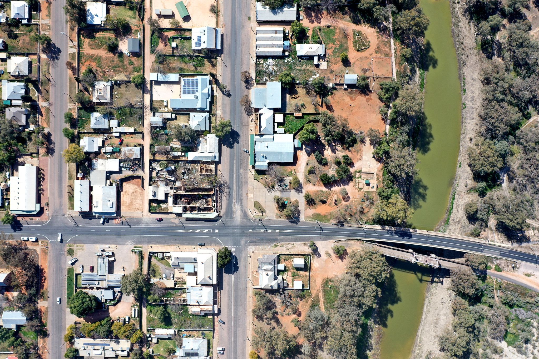 An aerial photograph of Wilcannia looking directly down on the town. Part of the town centre's street grid is visible, as well as the road bridge over the Darling River.