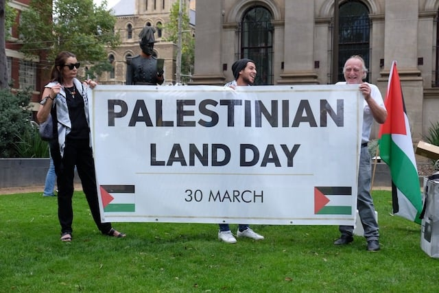 """A Palestininan Land Day banner being held by three people. The banner reads """"Palestininan Land Day 30 March"""" and is decorated with Palestinian flags."""
