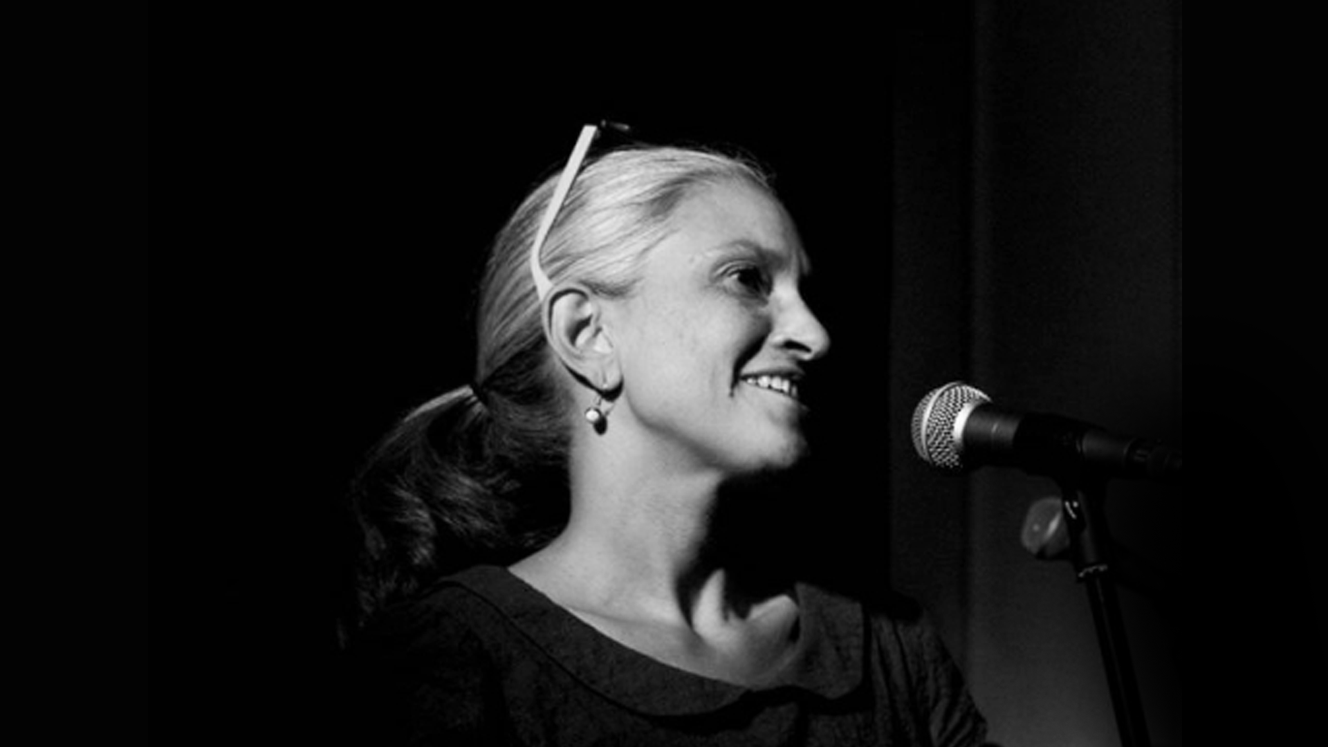 Black and white photograph of a woman speaking into a microphone. Only her face is clearly visible. She has fair hair and slender features.