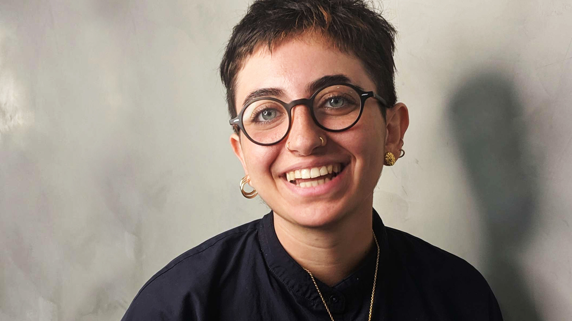 Image of a smiling person, with short dark hair and glasses. The guest presenter of 3CR Spoken Word, Lujayn Hourani
