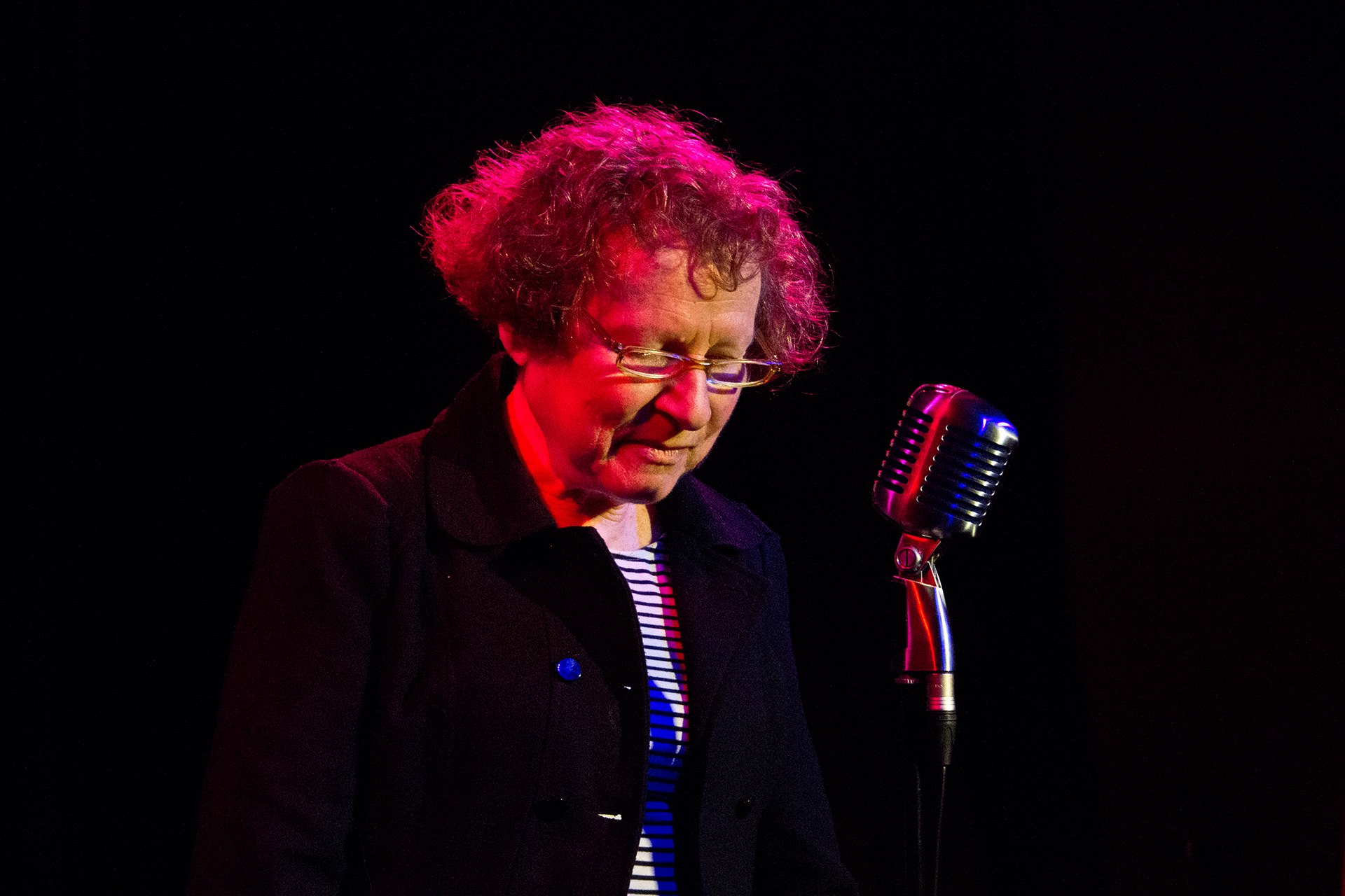 Picture of Ania Walwicz, an older person with olive skin and light hair, resting on stage in front of a microphone. She is about to speak.