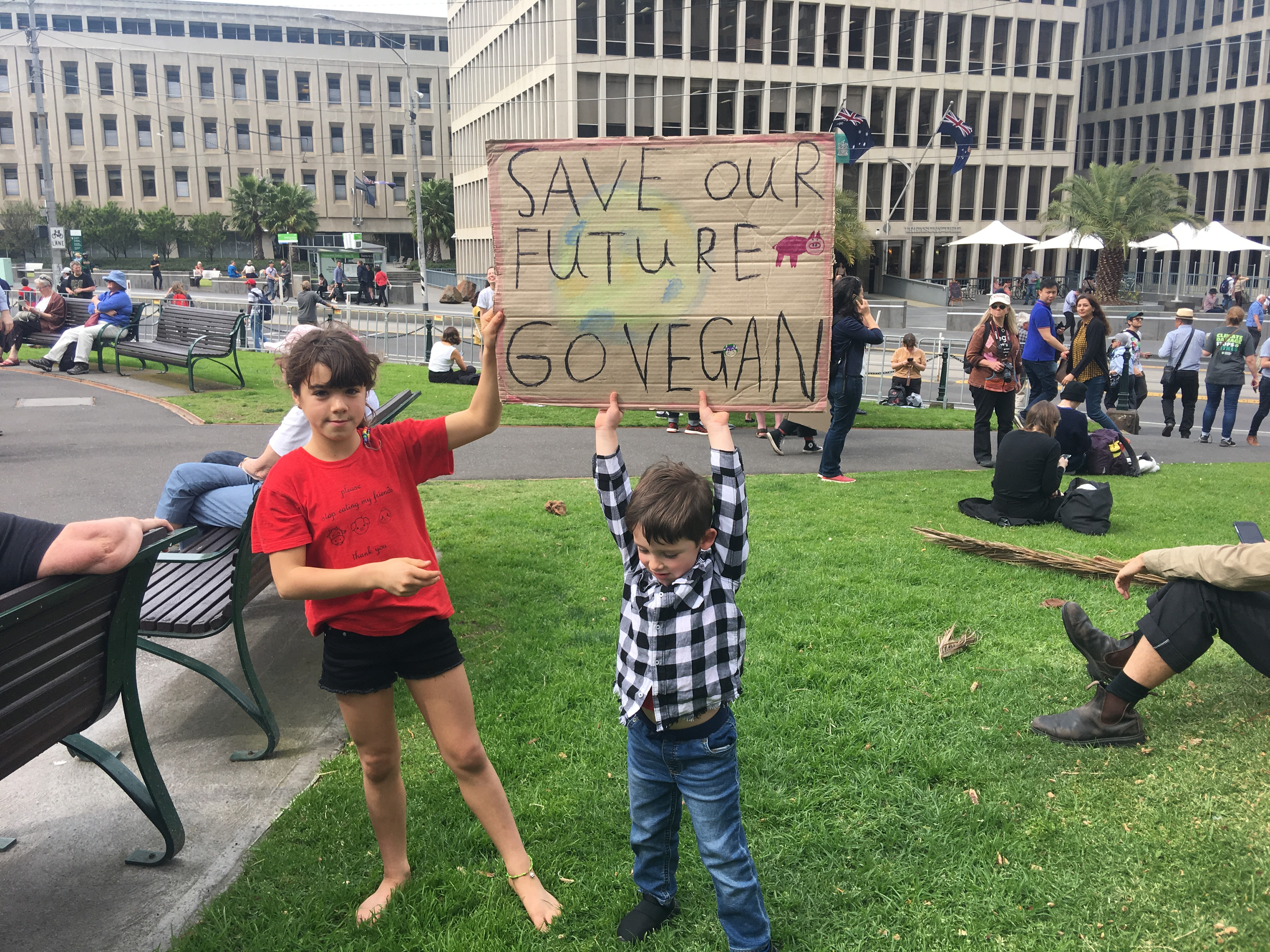 Kids holding up sign that reads, 'Save our Future, Go Vegan'.