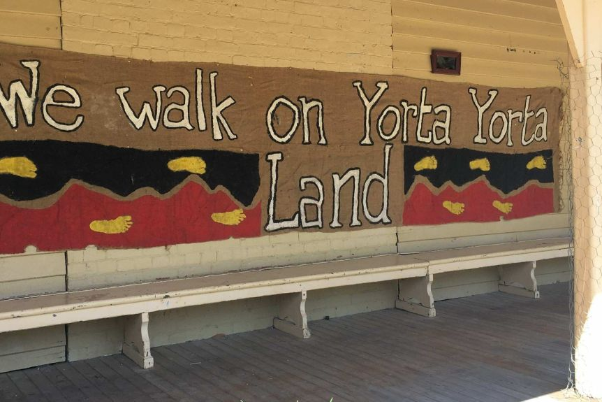 "Large banner reading ""We walk on Yorta Yorta land"" hung on a wall"