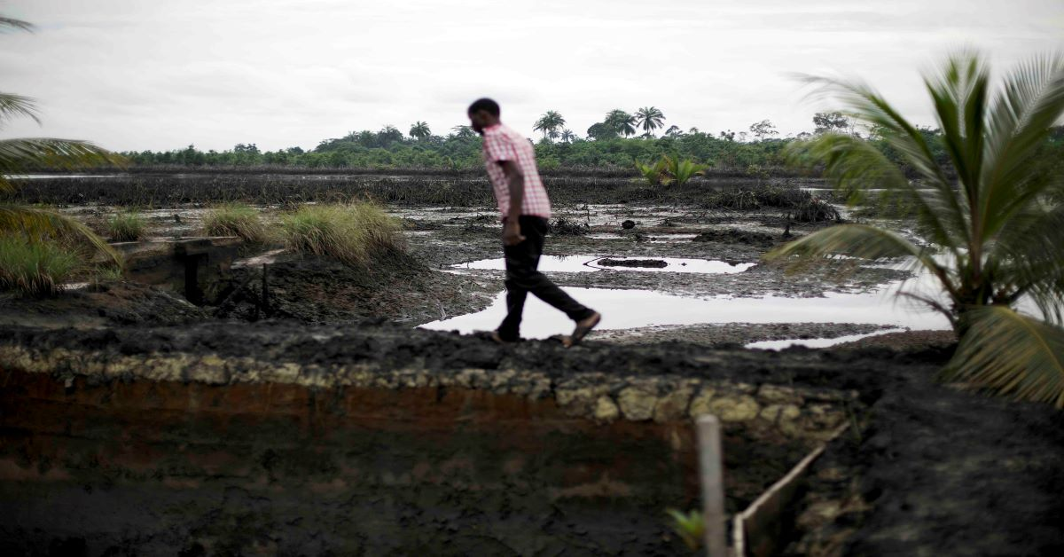 A man walks across a field polluted by oil