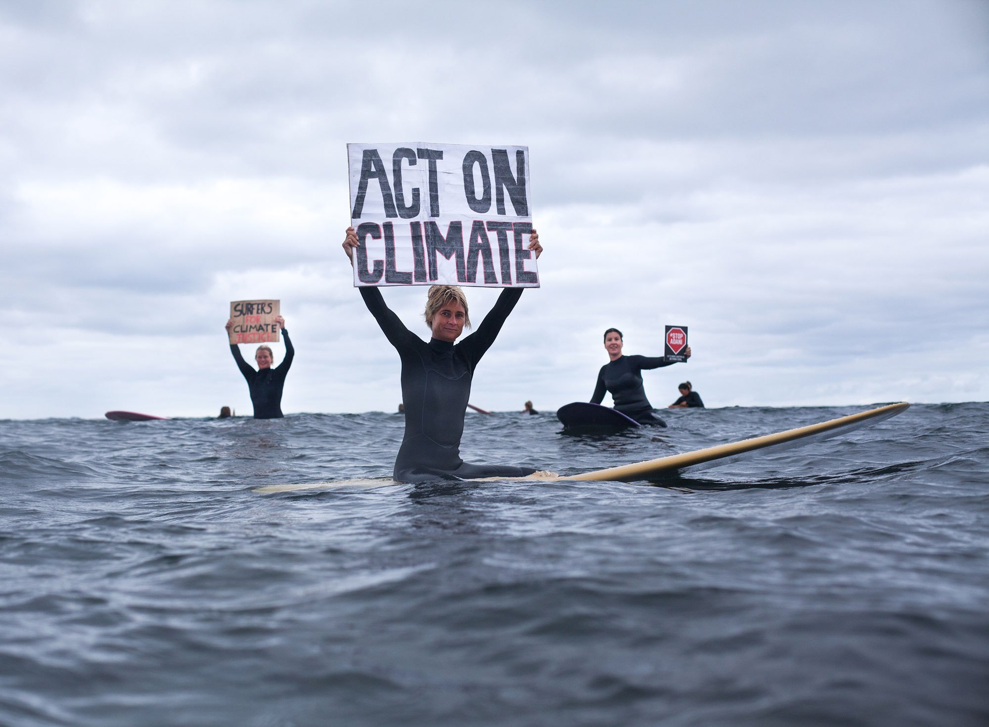 Surfers with an Act on Climate sign