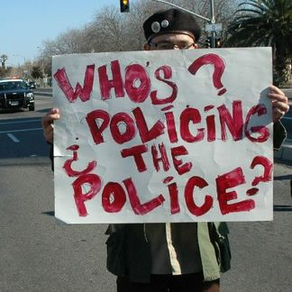 a person holding up a sign stating whos policing the police