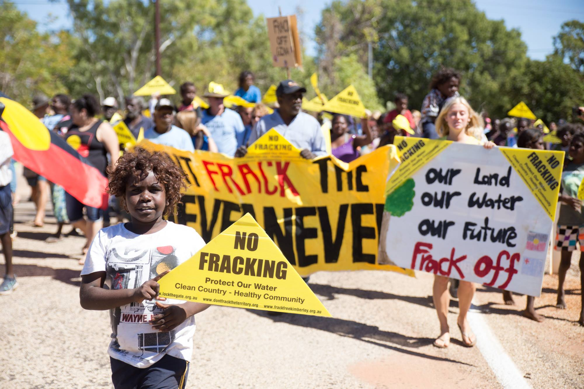 A small boy holds a No Fracking triangle in the foreground and the background is a group of people holding an anti-fracking banner