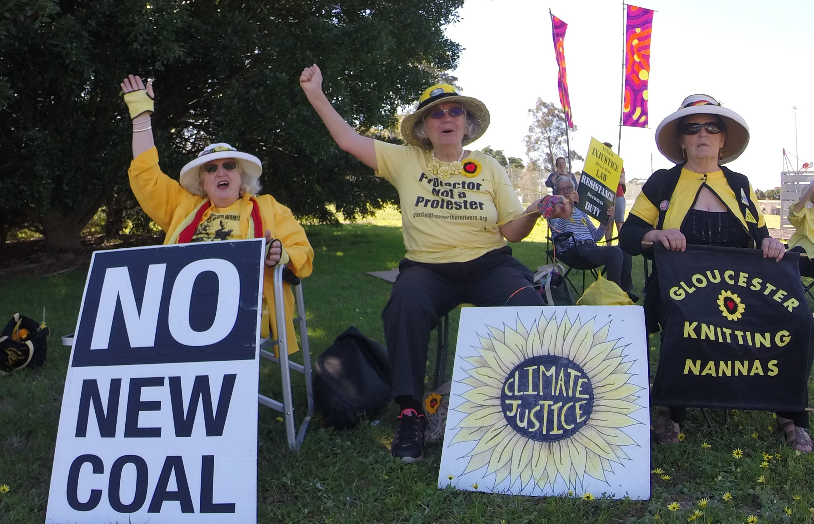 Three older women in yellow and black holding placards.