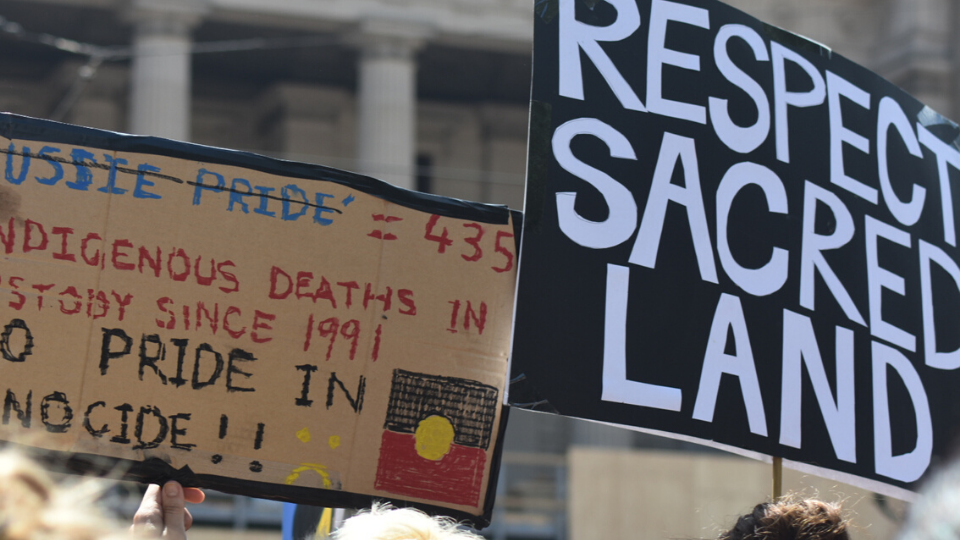 """rally placards saying """"respect sacred land"""" and """"435 Indigenous deaths in custody since 1991: No pride in genocide"""""""