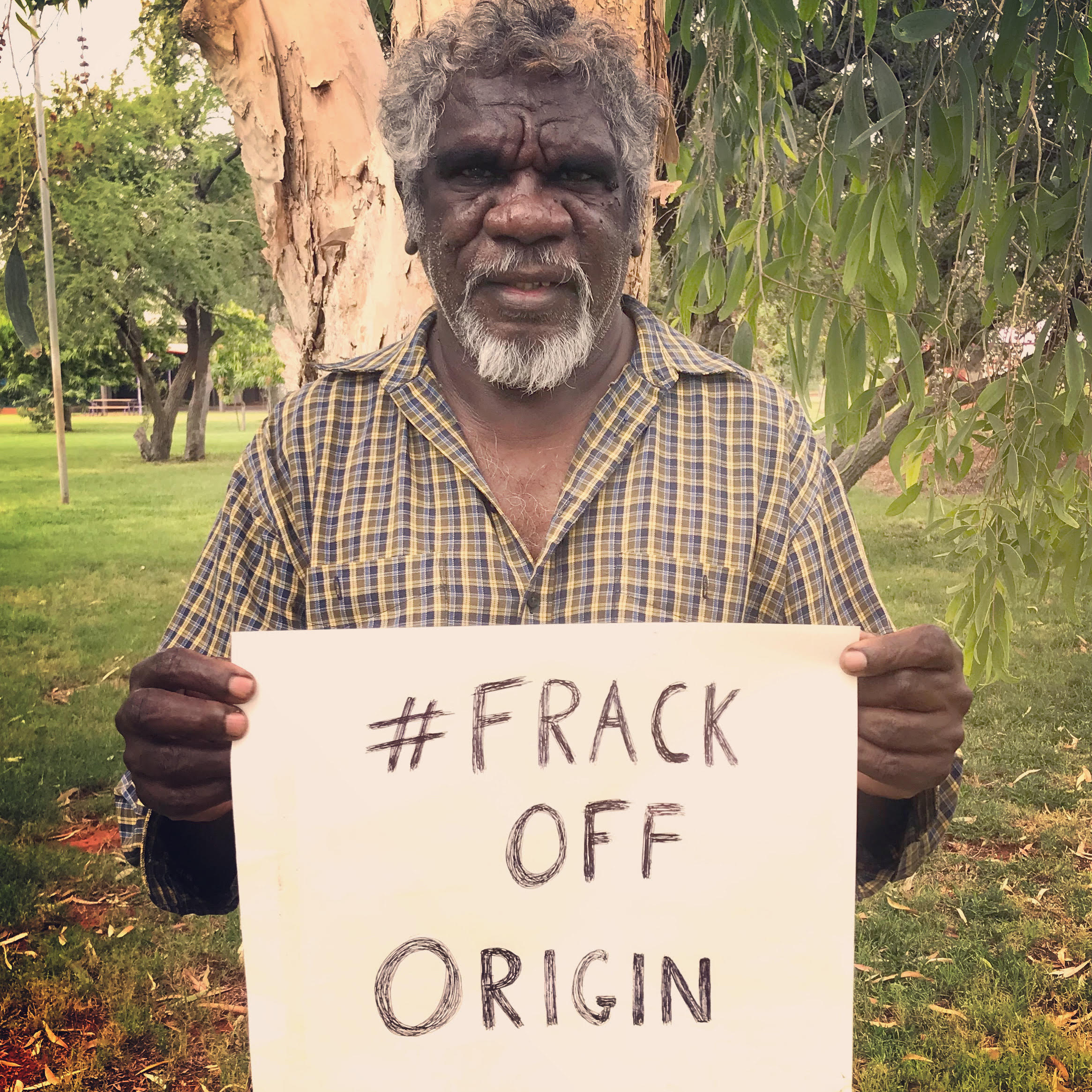 Mudburra Traditional Owner and Native Title Holder Ray Dimakarri Dixon from Marlinja NT holding a handwritten sign that says #frack off origin