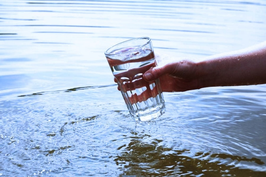 A glass of water held by a hand above a body of water