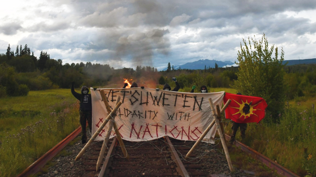 Several anonymous masked protesters wearing black pants, black hoodies, gloves and dark sunglasses stand defiantly with fists in the air at a barricade that has been erected across train tracks in a remote area. One of the protesters is holding up a Wet'suwet'en flag, which has a red background with a yellow sun, and an image of the profile of a Wet'suwet'en warrior wearing headdress in the centre of the sun. The barricade is constructed with 2 large, solid wooden tripods across tracks and a large banner st