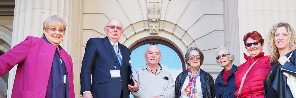 A group of retirement housing residents and advocates stand on the steps of Parliament House.