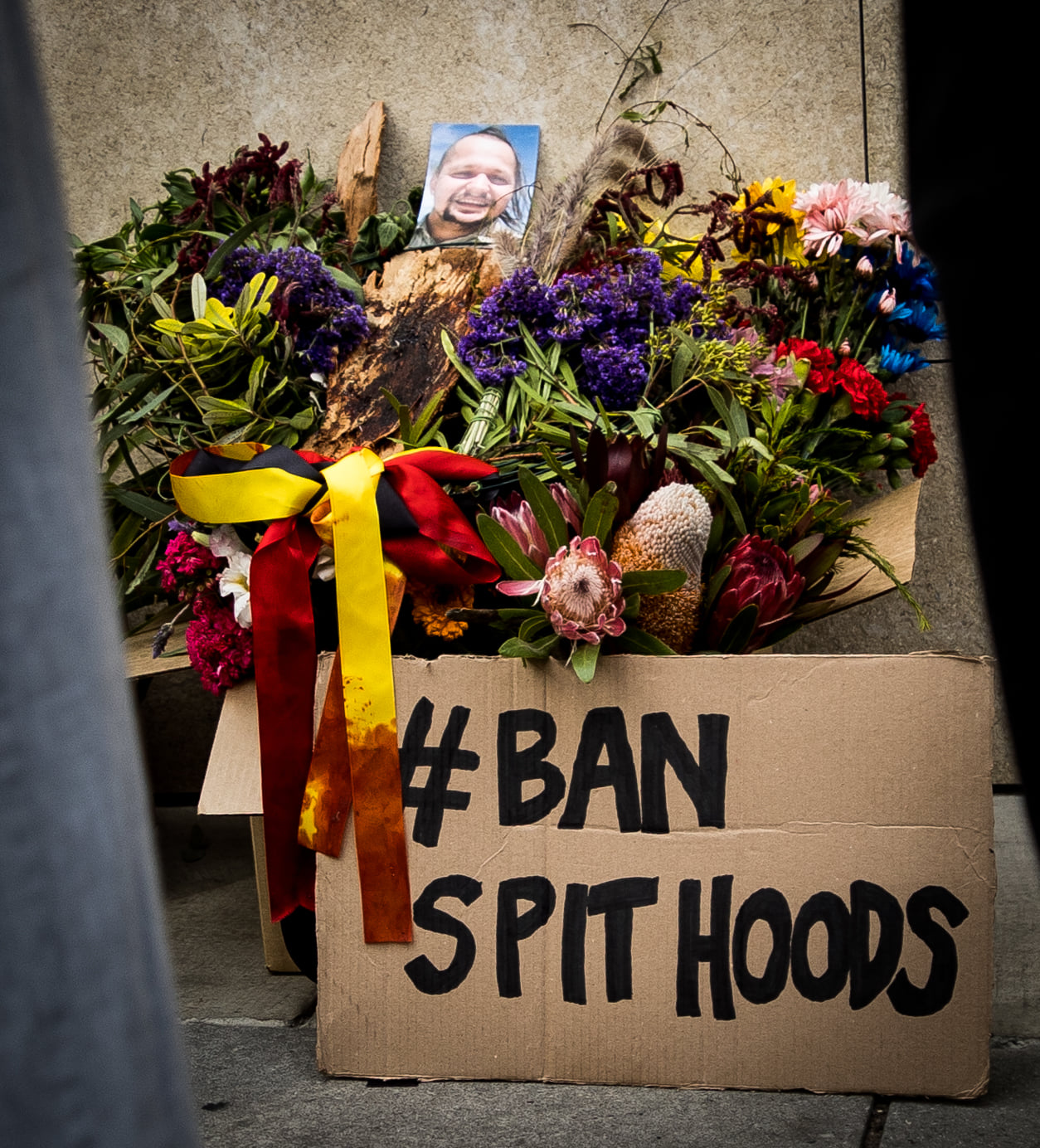 Ban Spithoods placard sits against a box of flowers, with a picture of Wayne Fella Morrison