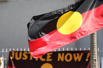 """Photo of an Aboriginal flag with the top of protest sign in the background that reads """"Justice Now"""""""