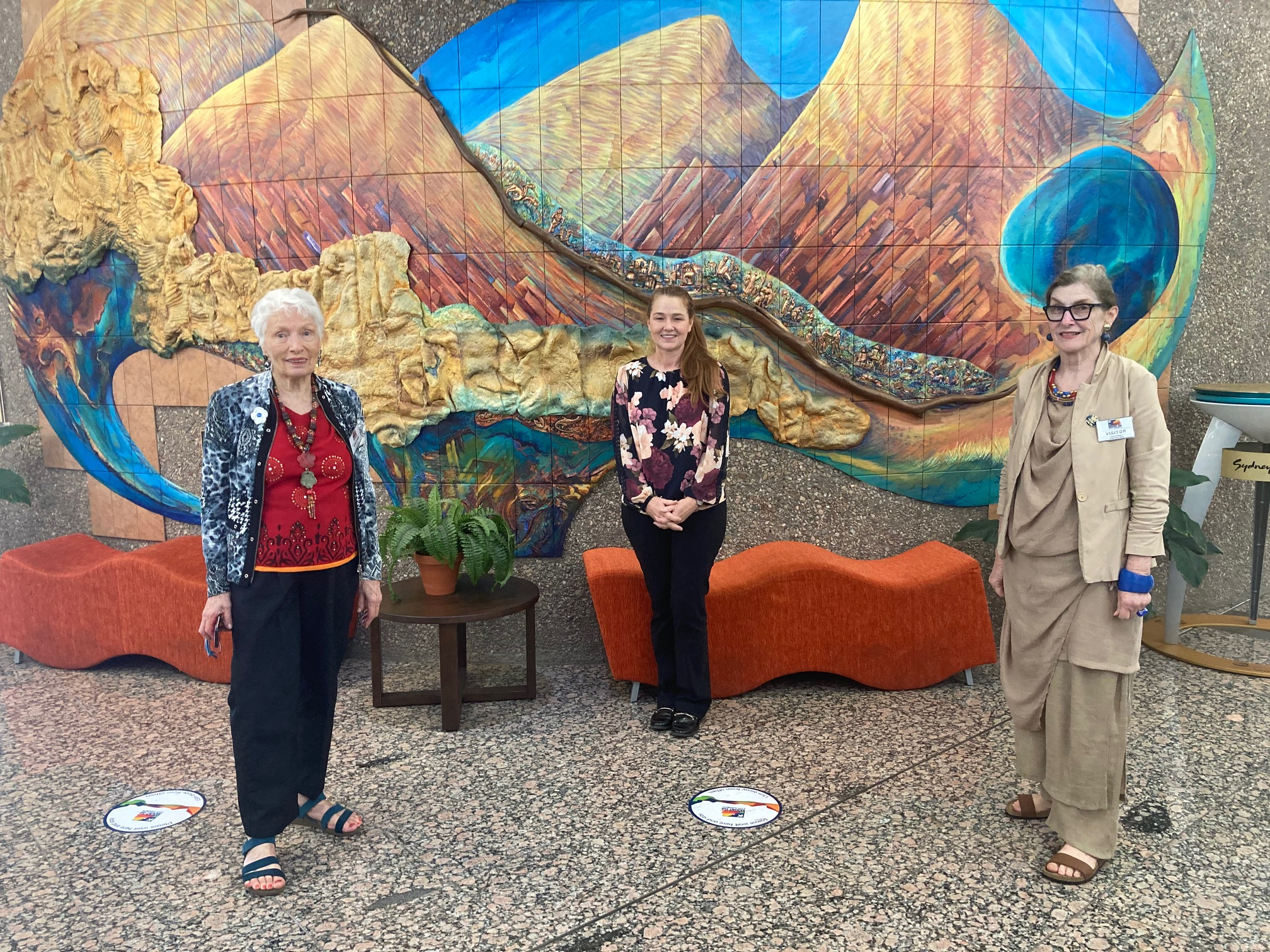 Three women, standing spaced out in front of a mural of mountains.