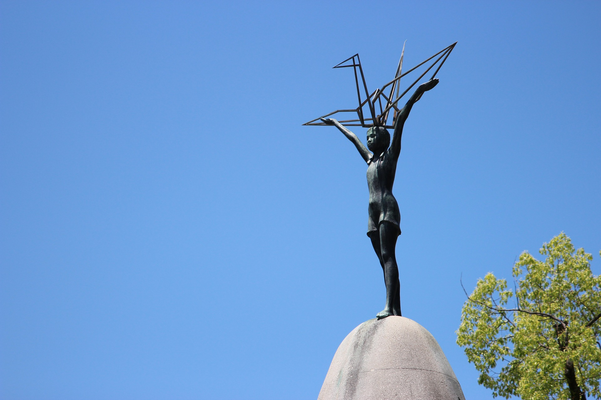 The Sadoko memorial in Hiroshima - a statue of a girl holding a metal crane, against a blue sky.