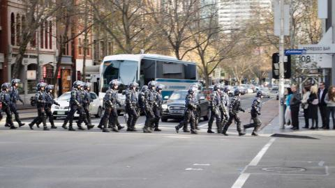 A photograph of members of Victoria Police Public Order Response Team crossing an intersection in single file, wearing full riot gear.