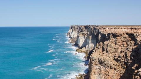 A photograph of the Great Australian Bight. To the right are steep rocky cliffs topped by a flat plain, and to the left is open water. The ocean is deep blue, growing darker towards the horizon. The sky is light blue and cloudless. Waves crash against the cliff face.
