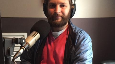 Pat Simons. White male, seated, facing the camera, pictured from the chest up. He is in a recording studio, wearing headphones and there is a microphone on the desk in front of him. He's wearing a pink jumper and a blue vinyl coat.