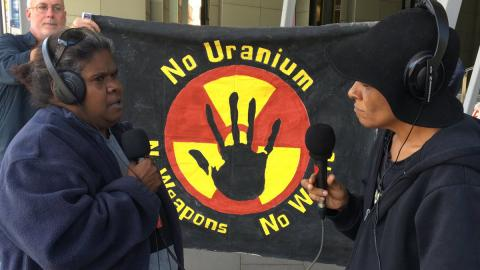 """3CR Presenter Viv Malo speaking with Aunty Vicki Abdullah (Tjiwarl Traditional Owner & co-chair of the Australian Nuclear free Alliance at  the IMARC blockade in Melbourne on Oct 28. They are facing each other wearing headphones and holding microphones standing in front of a banner that says """"no uranium, no weapons, no way""""."""