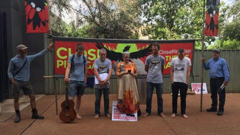 """The Pine Gap Peace Pilgrims praying before court. From left to right: Pauli Christie, Franz Downling, Jim Dowling, Margaret Pestorius, Tim Webb, Andy Paine, unknown. Pilgrims are standing in front of a banner that reads """"Close Pine Gap"""" and some aren't wearing shoes. Franz holds a guitar. Margaret is speaking."""
