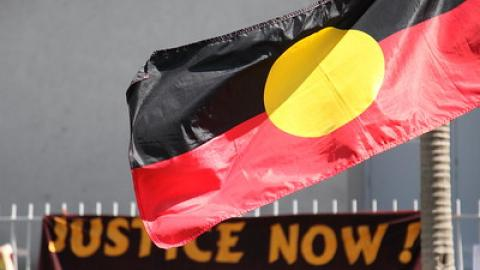 "Photo of an Aboriginal flag with the top of protest sign in the background that reads ""Justice Now"""