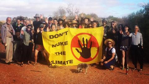 "Group of about thirty people holding banner that says ""Don't Nuke the Climate"", standing in front of sand dunes and bush at Woomera"