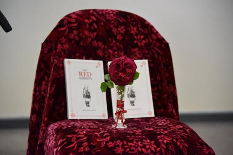Red rose in a vase, resting on a chair, in front of two copies of the book, The Red Ribbon