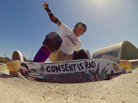 """A low-angle photograph of a skateboarder in the middle of a trick on the rim of a skate park bowl. You can see the bottom of their board, which has a large sticker on it reading """"Consent is Rad""""."""