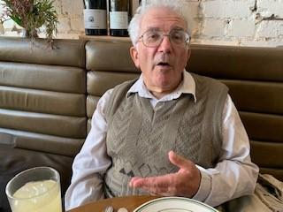 Image of an older man with glasses wearing a cream long sleeved shirt with a colour with a taupe knitted vest over the top. The man is at a cafe sitting in front of him is a beverage and a plate. He looks like he is about to speak. In the background are some wine bottles as decoration.