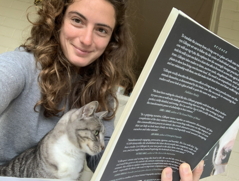 Davita with a cat sitting in her lap both apparently reading a science book.