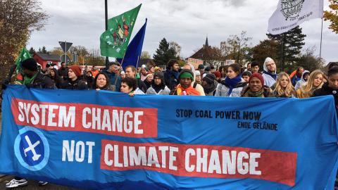 Six POC are carrying a large banner and leading a huge protest march with up to hundred people visible behind them. The banner is blue and red, with black and white text. It says 'Stop cola power now—Ende Gelände' and 'System change, not climate change', and also depicts the Ende Gelände logo with crossed mallet and pick axe in a circle.