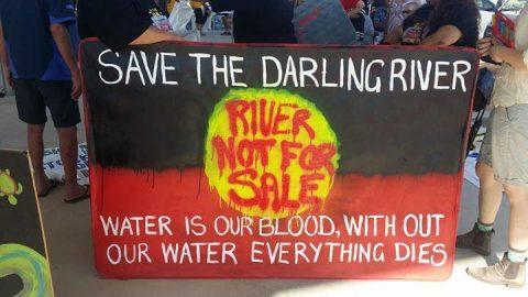 Banner of Aboriginal flag saying 'Save the Darling River; River not for sale; Water is our blood, without water everything dies'