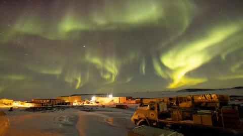 Aurora Australis over Davis station: In the foreground is heavy machinery and buildings and structures of the station with the skyline and playful and intricate light patterns of the aurora bearing down on them