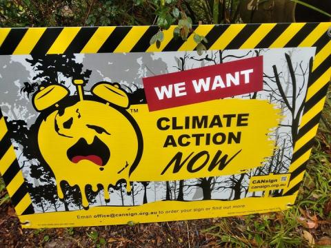 A yellow and black sign with a melting clock with alarmed face. Climate Action Now