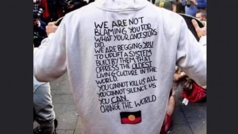 """Photograph of protestor's torso from the back. They are wearing a hoodie that says """"We are not blaming you for what your ancestors did. We are begging you to uplift a system built by them that oppress the oldest living culture in the world. You can not kill us all. You can not silence us. You can change the world."""