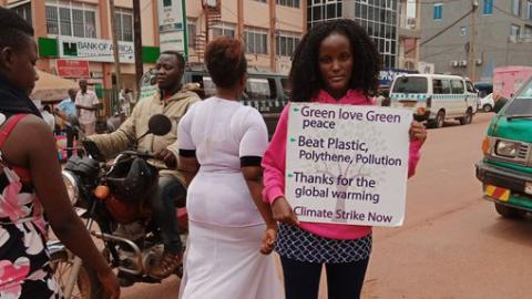 Vanessa Nakate is standing on the street holding a protest sign that says, 'Green love, green peace; beat plastic, polyethylene, pollution; thanks for the global warming; climate strike now.' in the background are people walking by, traffic & buildings.