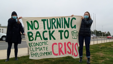 """Two young people wearing dark toned warm winter clothes and covid protection face masks are holding a banner up on the side of a busy highway. The banner says """"No Turning Back to economic, climate, employment CRISIS""""."""