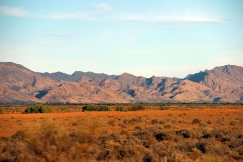 Image taken from moving vehicle, so dry red earth and grasslands in foreground are slightly blurred. Behind are dramatic hills with many peaks, bush covered at the back and less bushy, and dry looking in front.