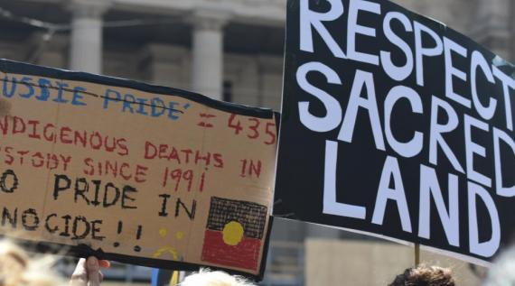 Invasion Day 2020 signs: 'Respect Sacred Land' & 'No Pride in Genocide'